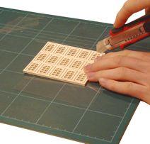 Trenn die Fensterrahmen voneinander, indem du mit einem scharfen Bastelmesser die Haltegrate durchtrennst.
